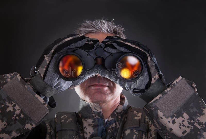 Soldado maduro que olha através dos binóculos fotos de stock