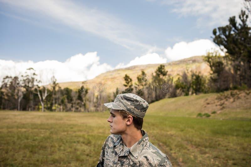 Soldado militar que guarda en campo de bota foto de archivo