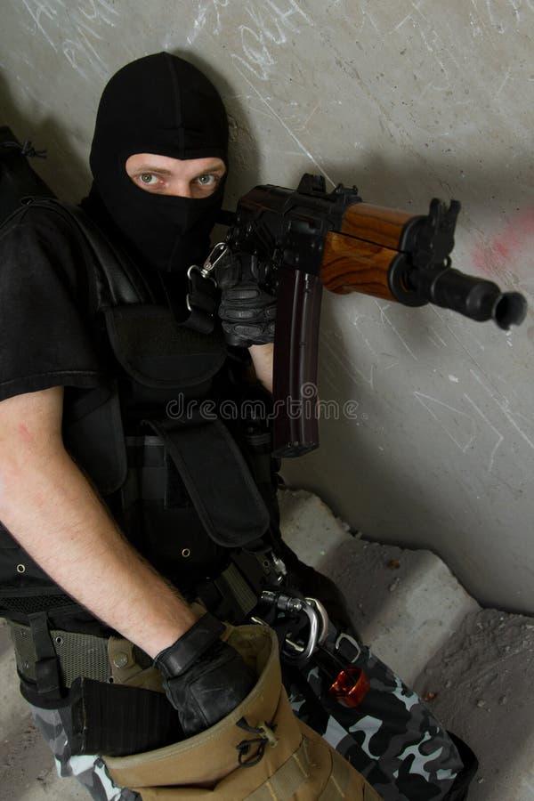 Soldado na máscara preta que recarrega o rifle de AK-47 imagem de stock royalty free