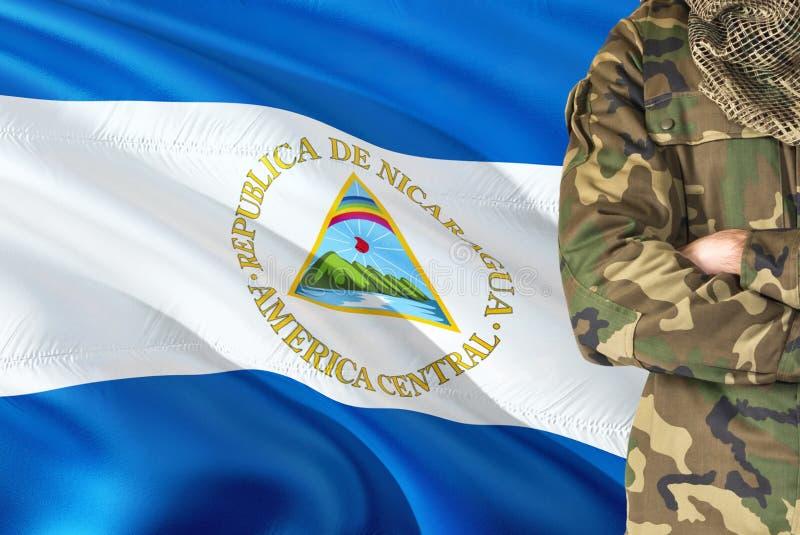 Soldado nicaraguense cruzado dos braços com a bandeira de ondulação nacional no fundo - tema militar de Nicarágua foto de stock