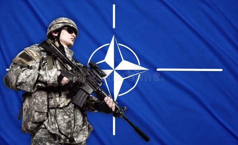 Soldado no fundo da bandeira da OTAN fotografia de stock
