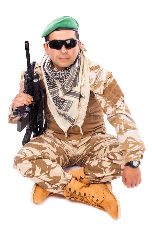 Soldado novo com a boina e os vidros que guardaram um automático foto de stock royalty free