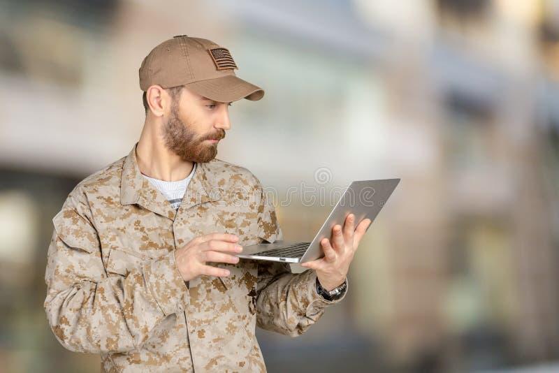 Soldado novo do exército com um portátil foto de stock