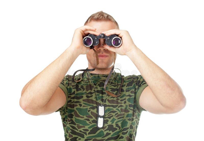 Soldado novo do exército que olha através dos binóculos foto de stock