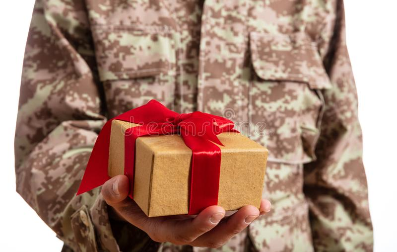 Soldado novo que guarda uma posição do presente do Natal no fundo branco fotos de stock