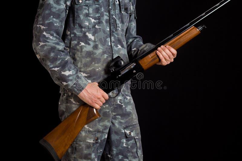 Soldado o cazador en un fondo negro, aislado, espacio de la copia Hombre joven con un arma Un soldado en uniforme militar con una fotos de archivo libres de regalías