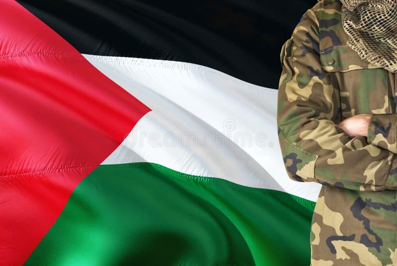 Soldado palestino cruzado dos braços com a bandeira de ondulação nacional no fundo - tema militar de Palestina imagem de stock