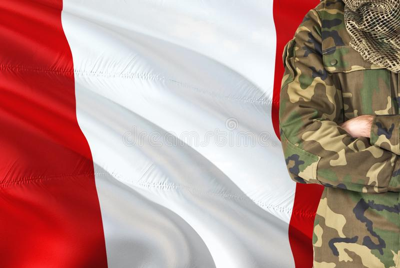 Soldado peruano cruzado dos braços com a bandeira de ondulação nacional no fundo - tema de Peru Military fotografia de stock