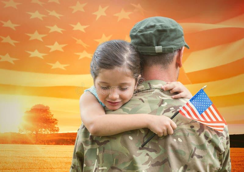 soldado que abraza a la hija en el campo con la bandera de los E.E.U.U. imagenes de archivo