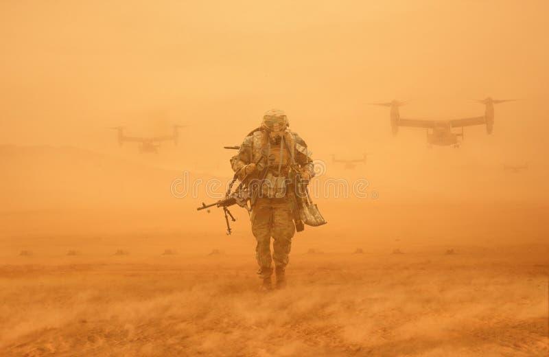 Soldado que anda no deserto com as engrenagens da guerra imagem de stock royalty free