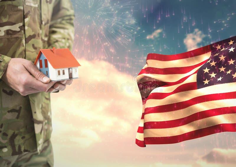Soldado que guarda uma casa pequena perto da bandeira americana foto de stock