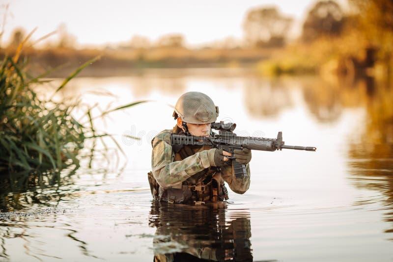 Soldado que se mueve a través del agua y que tiene como objetivo al enemigo fotos de archivo