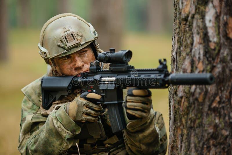 Soldado que sostiene un arma que apunta con el alcance fotografía de archivo libre de regalías