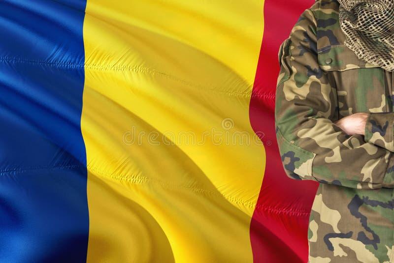 Soldado rumano cruzado de las armas con la bandera que agita nacional en el fondo - tema militar de Rumania foto de archivo libre de regalías