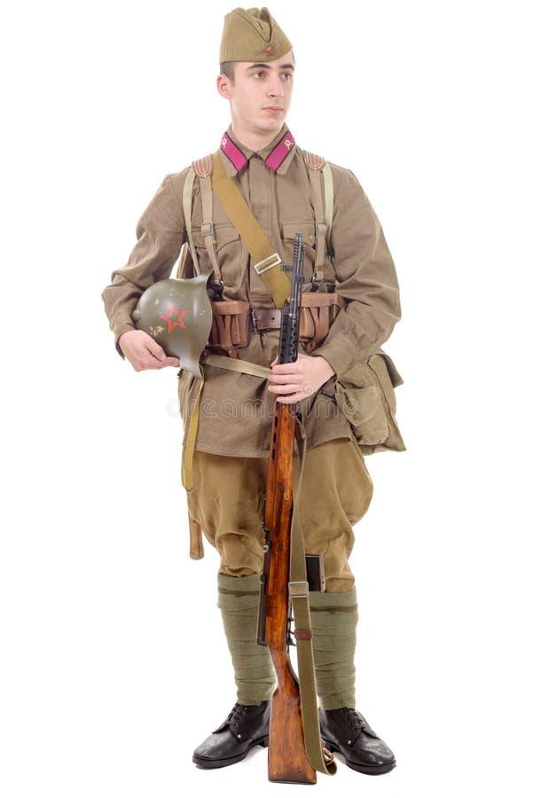 Soldado soviético joven con el rifle en el fondo blanco imagen de archivo