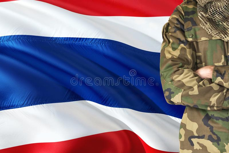 Soldado tailandês cruzado dos braços com a bandeira de ondulação nacional no fundo - tema militar de Tailândia fotografia de stock