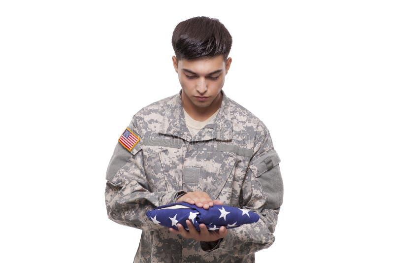 Soldado triste con una bandera americana fotografía de archivo