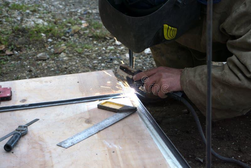 Soldador, artesano, erigiendo el soldador de acero industrial de acero técnico en la fábrica técnica, imagenes de archivo