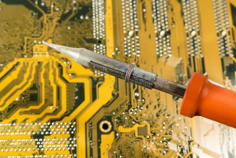 Soldador con la manija roja sobre una placa de circuito impresa fotografía de archivo libre de regalías