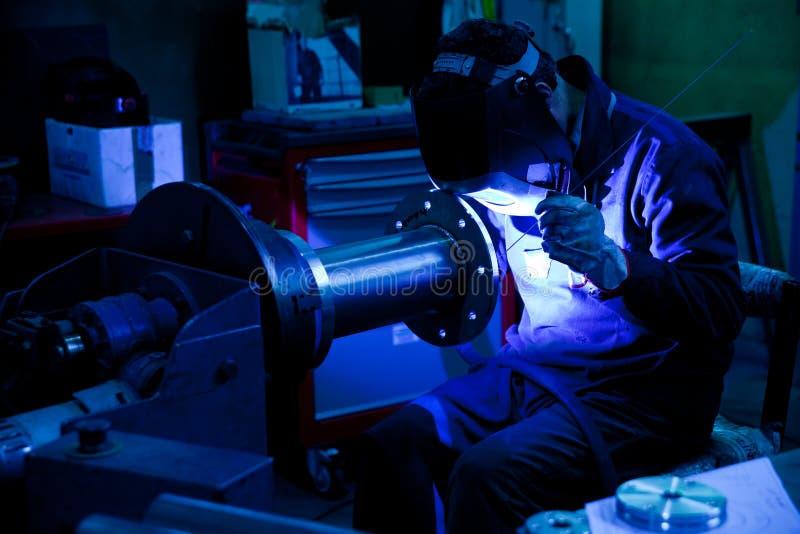 Soldador en el trabajo en surrondings industriales. imagen de archivo