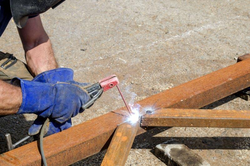 Soldador na solda do trabalho uma construção do ferro em um armazém do metal foto de stock royalty free