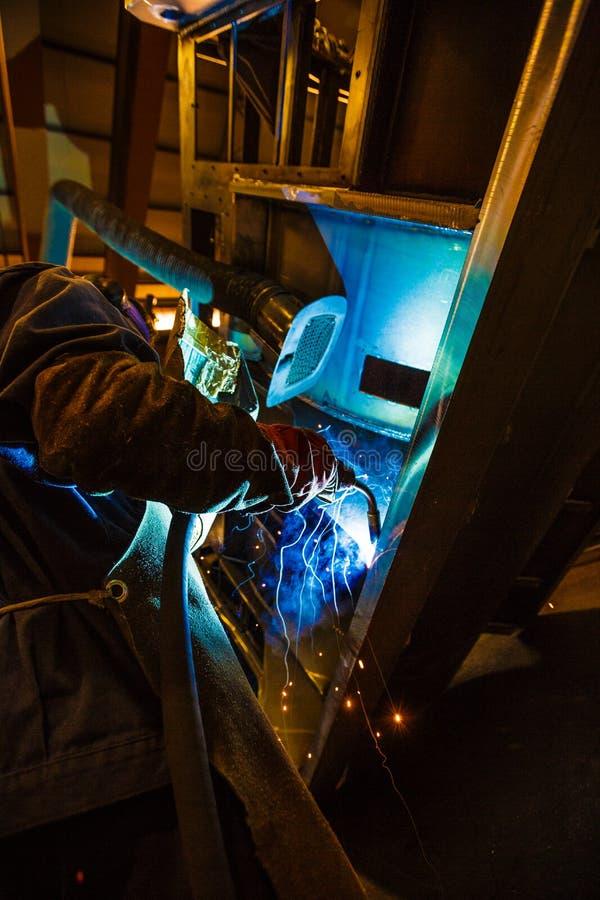 Soldador no trabalho em surrondings industriais imagens de stock