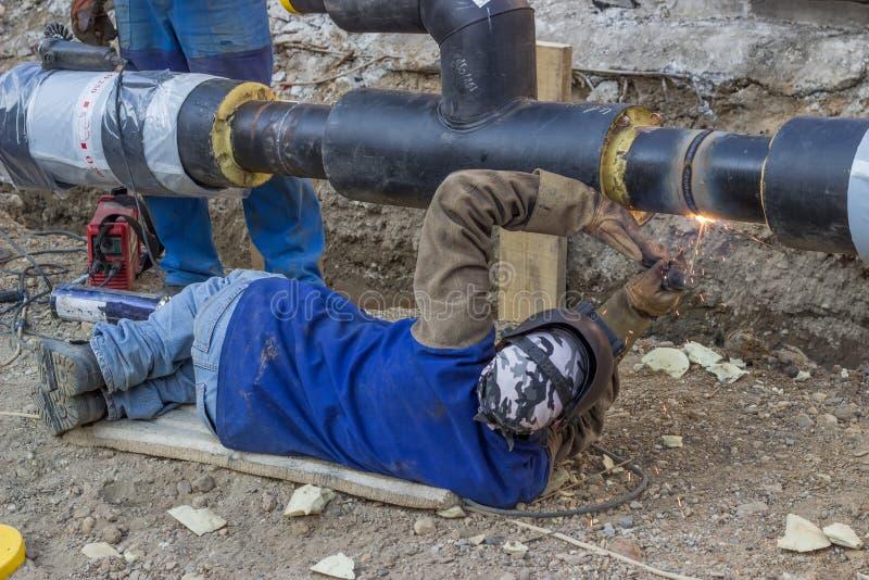 Soldador que suelda con autógena la tubería de acero subterráneo que miente en la tierra imagen de archivo libre de regalías
