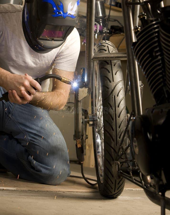 Soldador que trabalha na motocicleta imagem de stock royalty free
