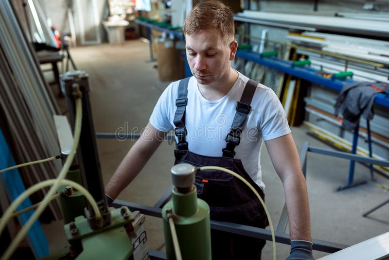 Soldadora de funcionamiento del trabajador en fábrica fotos de archivo