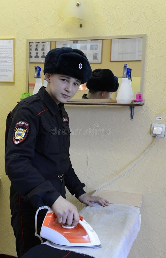 Soldados das tropas internas que afagam o formulário na sala de serviço público das casernas imagem de stock