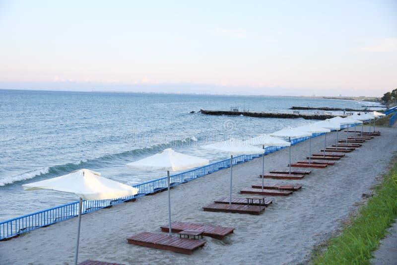 Soldados de madeira e guarda-chuvas na praia do mar fotografia de stock royalty free