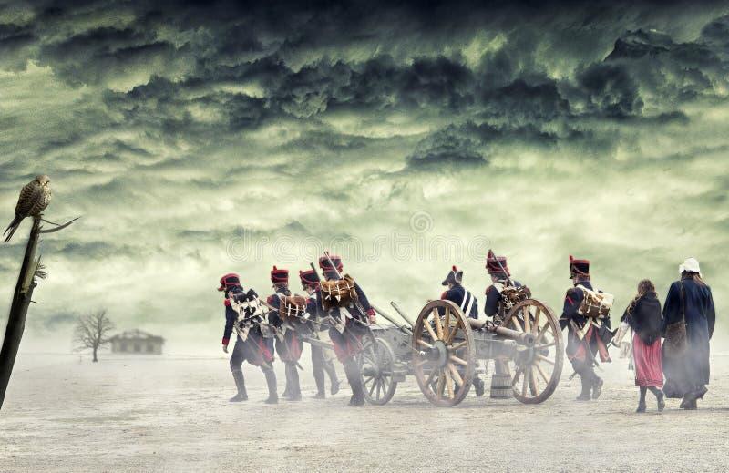 Soldados de Napoleão e mulheres que marcham e que puxam um canhão na terra lisa, campo com nuvens tormentosos Passeio dos soldado imagem de stock
