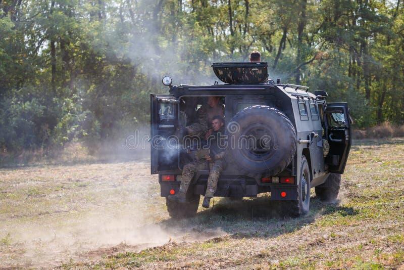 Soldados do destacamento do objetivo especial que conduzem em um carro armado através do campo e que disparam em uma metralhadora fotos de stock royalty free