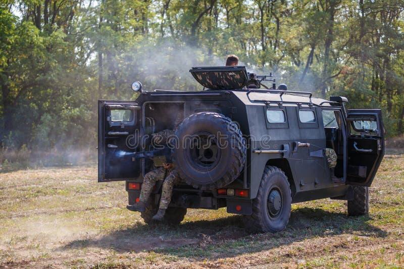 Soldados do destacamento do objetivo especial que conduzem em um carro armado através do campo e que disparam em uma metralhadora fotos de stock