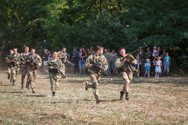 Soldados do destacamento pequeno do objetivo especial com as armas em suas mãos corridas no campo imagem de stock