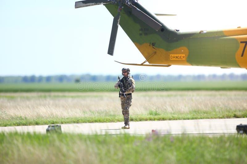 Soldados do exército romeno patrulham uma base aérea militar, perto de um helicóptero militar, durante uma perfuração fotografia de stock royalty free