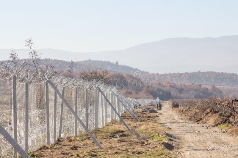 Soldados macedônios que inspecionam a parede da cerca da beira na beira de Macedônia Grécia construída durante a crise do refugia foto de stock