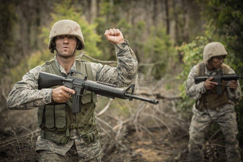 Soldados militares durante ejercicio de formación con el arma fotos de archivo