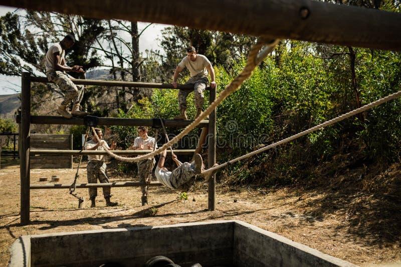 Soldados militares novos que praticam a corda que escala durante o curso de obstáculo fotografia de stock royalty free