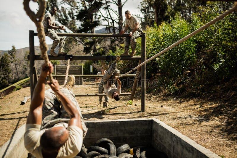 Soldados militares novos que praticam a corda que escala durante o curso de obstáculo fotografia de stock