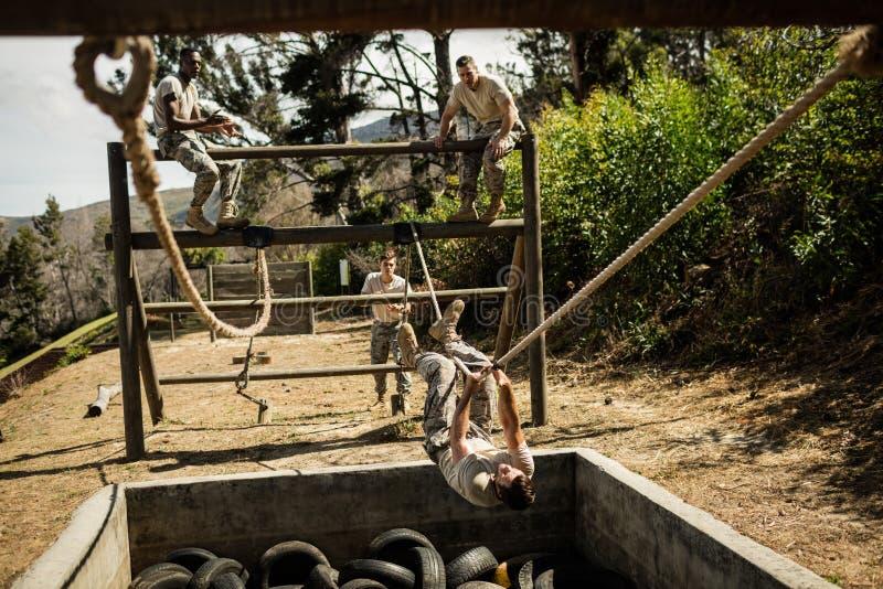 Soldados militares novos que praticam a corda que escala durante o curso de obstáculo imagem de stock royalty free