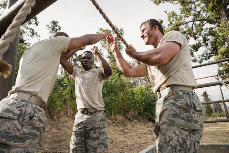 Soldados militares novos que praticam a corda que escala durante o curso de obstáculo imagens de stock royalty free