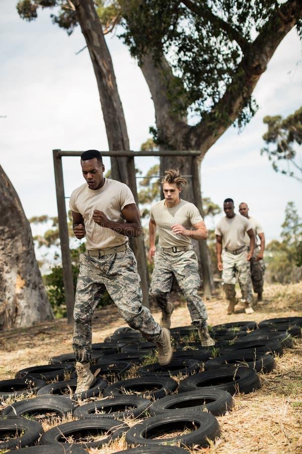 Soldados militares novos que praticam o curso de obstáculo do pneumático imagem de stock