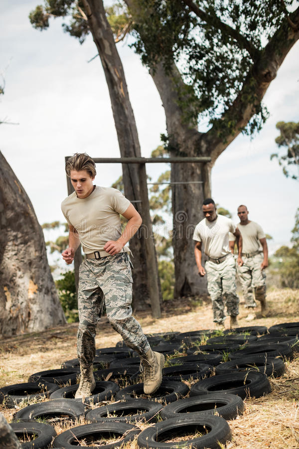 Soldados militares novos que praticam o curso de obstáculo do pneumático fotografia de stock royalty free