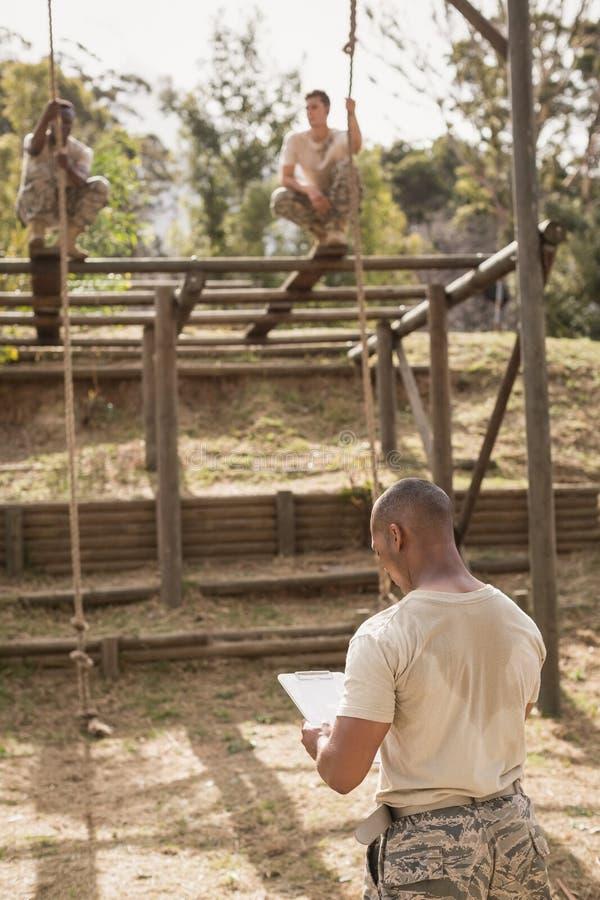 Soldados militares que escalam a corda durante o treinamento do curso de obstáculo imagem de stock