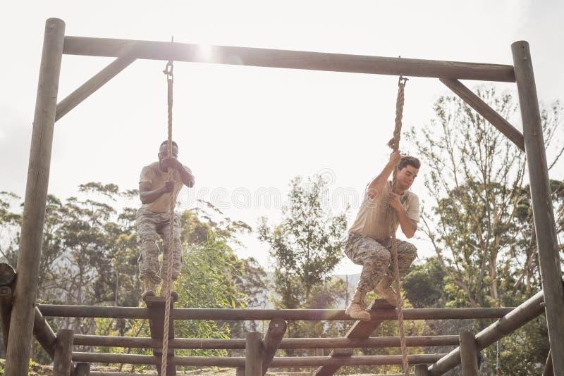 Soldados militares que escalam a corda durante o treinamento do curso de obstáculo fotografia de stock