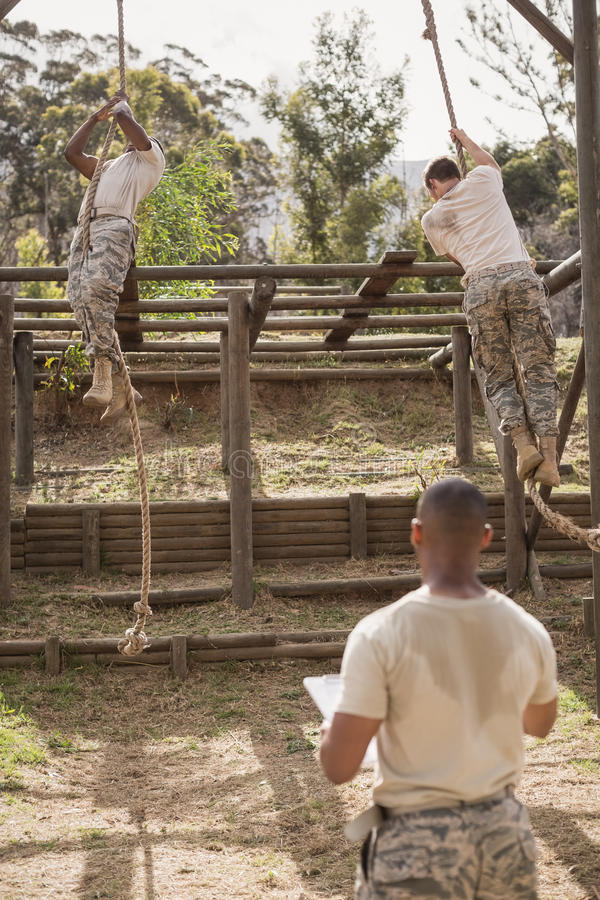 Soldados militares que escalam a corda durante o treinamento do curso de obstáculo imagens de stock royalty free