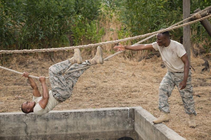 Soldados militares que escalam a corda durante o treinamento do curso de obstáculo foto de stock