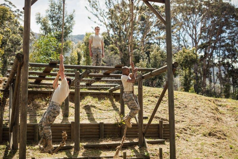 Soldados militares que treinam a escalada da corda foto de stock