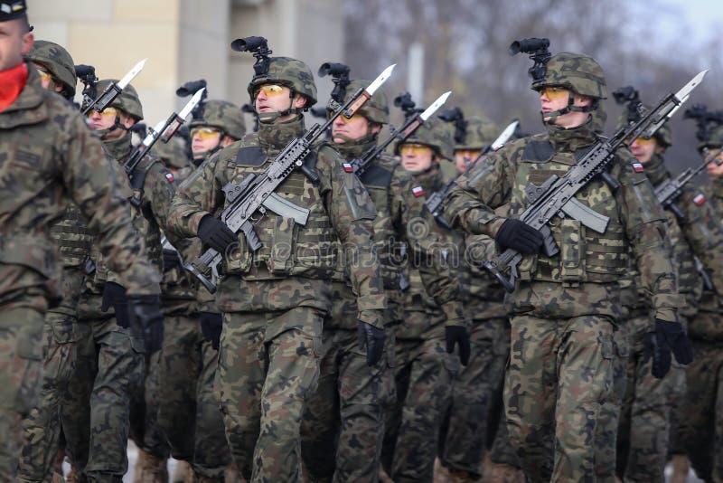 Soldados poloneses com as câmeras em capacetes e armadas com as espingardas de assalto de Beryl foto de stock